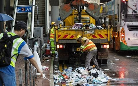 Workers clear trash outside the Legislative Council building a day after violent clashes over a proposed extradition bill in Hong Kong, China - Credit: Justin Chin/Bloomberg