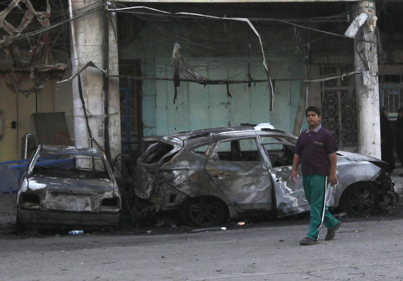 An Iraqi walks by the site of a car bomb attack at al-Keefah street in Baghdad, Iraq, Tuesday, May 28, 2013. A coordinated wave of car bombings tore through mostly Shiite areas of Baghdad on Monday, killing and wounding dozens of people, as insurgents step up the bloodshed roiling Iraq. (AP Photo/ Hadi Mizban)