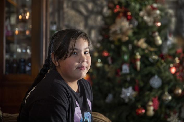 A girl sits in front of a Christmas tree in her home