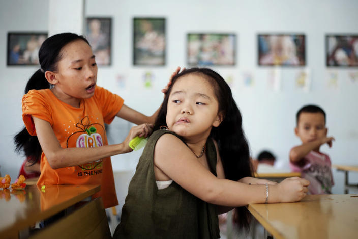 In this photo taken Aug. 7, 2012, Ho Thi Lang, left, combs Ngo Diep Uyen's hair after her nap at a rehabilitation center in Danang, Vietnam. The children were born with physical and mental disabilities that the center's director said were caused by their parents' exposure to the chemical dioxin in the defoliant Agent Orange. Washington was slow to respond, but on Thursday the U.S. for the first time will begin cleaning up leftover dioxin that was stored at the former military base, now part of Danang's airport. (AP Photo/Maika Elan)