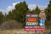 Smoke rises from mountain ridges while a sign warns of fire danger as a wildfire burns Thursday, Oct. 22, 2020, near Fraser, Colo. (AP Photo/David Zalubowski)