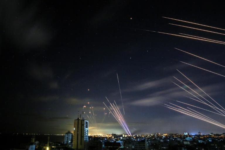 The Israeli Iron Dome missile defence system, on the left, intercepts rockets fired by the Hamas movement towards southern Israel from Beit Lahia in the northern Gaza Strip