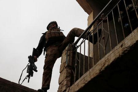 An Iraqi special forces soldier climbs a house during a battle with Islamic State militants in Mosul, Iraq March 2, 2017. REUTERS/Goran Tomasevic