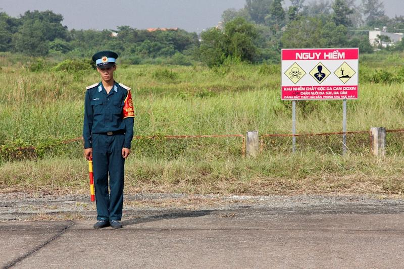 A Vietnamese soldier stands next to a sign warning of toxic hazard at Bien Hoa air base, on the outskirts of Ho Chi Minh City
