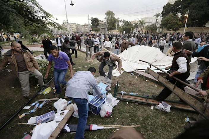 FILE - In this Wednesday, Dec. 5, 2012 file photo, supporters of Egyptian President Mohammed Morsi remove tents of opposition protesters outside the presidential palace, in Cairo, Egypt. For most of the 85 years since its inception, the Muslim Brotherhood operated secretively as an outlawed group, working underground and often repressed by governments. But even after its political success since Hosni Mubarak's ouster, the group is still suspected of carrying on secretive operations. (AP Photo/Hassan Ammar, File)