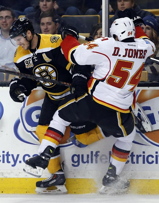 Boston Bruins center David Krejci (46) collides with Calgary Flames right wing David Jones (54) along the boards during the first period of an NHL hockey game in Boston, Tuesday, Dec. 17, 2013. (AP Photo/Elise Amendola)