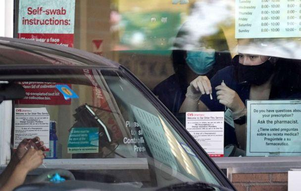 PHOTO: Pharmacy workers give instruction on how to administer a self COVID-19 nasal swab test at a drive-up CVS pharmacy in Dallas, Sept. 18, 2020. (Lm Otero/AP)