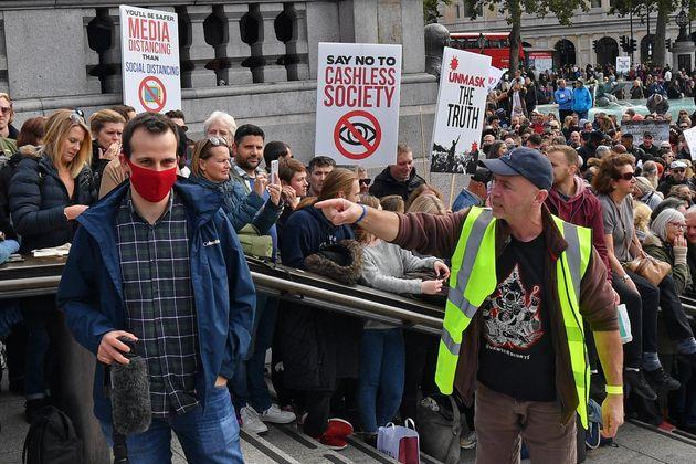 A protester (R) gestures to a member of the media (L) as he complains about the wearing of a mask, in Trafalgar Square.