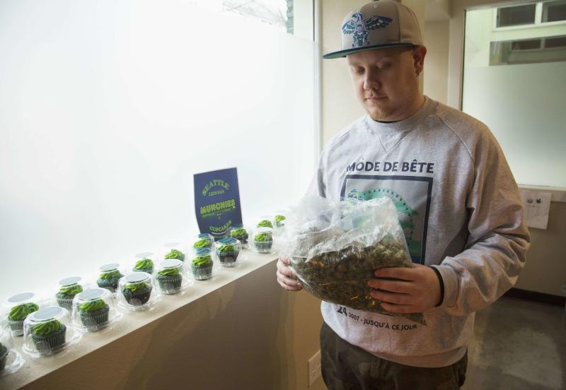 """Nate Johnson, managing owner of the Queen Anne Cannabis Club, carries a bag of a marijuana strain called """"Beast Mode OG"""", named after NFL player Marshawn """"Beast Mode"""" Lynch of the Seattle Seahawks, in Seattle, Washington January 28, 2014. For Nate Johnson, the excitement surrounding the upcoming Super Bowl is two-fold. Not only are his hometown Seattle Seahawks taking on the Denver Broncos - football teams representing two major U.S. cities where recreational pot use is legal - but his medical weed dispensary is seeing green. Demand for """"Beast Mode"""" - a strain named in honor of the Seahawks' hard-hitting running back, Marshawn Lynch - has been high at his Queen Anne Cannabis Club in Seattle, Johnson said, while pot-laced blue-and-green cupcakes are also selling fast. REUTERS/Jason Redmond (UNITED STATES - Tags: DRUGS SOCIETY BUSINESS SPORT FOOTBALL FOOD)"""