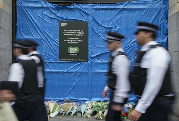 Police officers walk past floral tributes in Borough Market after the attack (Picture: PA)