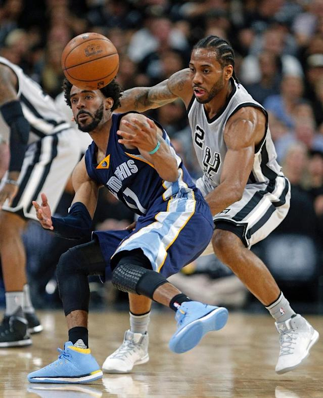 Kawhi Leonard (R) of the San Antonio Spurs attempts to steal the ball from Mike Conley of the Memphis Grizzlies in Game One of the Western Conference quarter-finals during the 2017 NBA Playoffs, at AT&T Center in San Antonio, on April 15 (AFP Photo/Ronald Cortes)