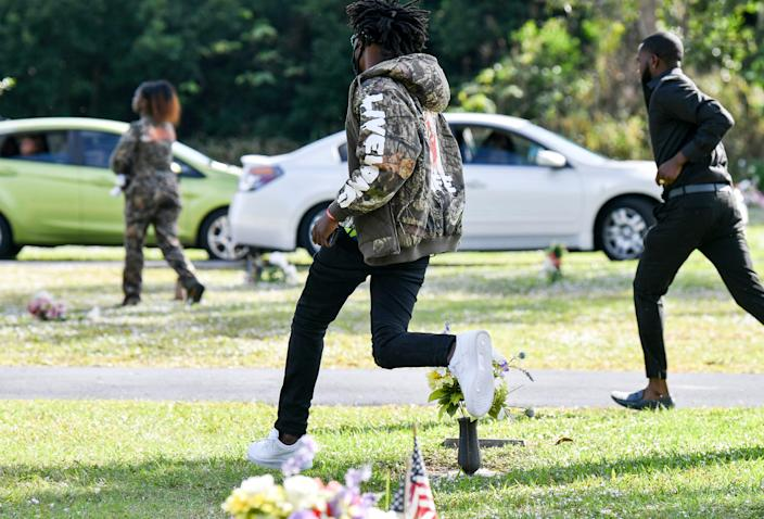 Spectators flee after a shot was fired during a funeral service for Sincere Pierce at Riverview Memorial Gardens in Cocoa, Florida.