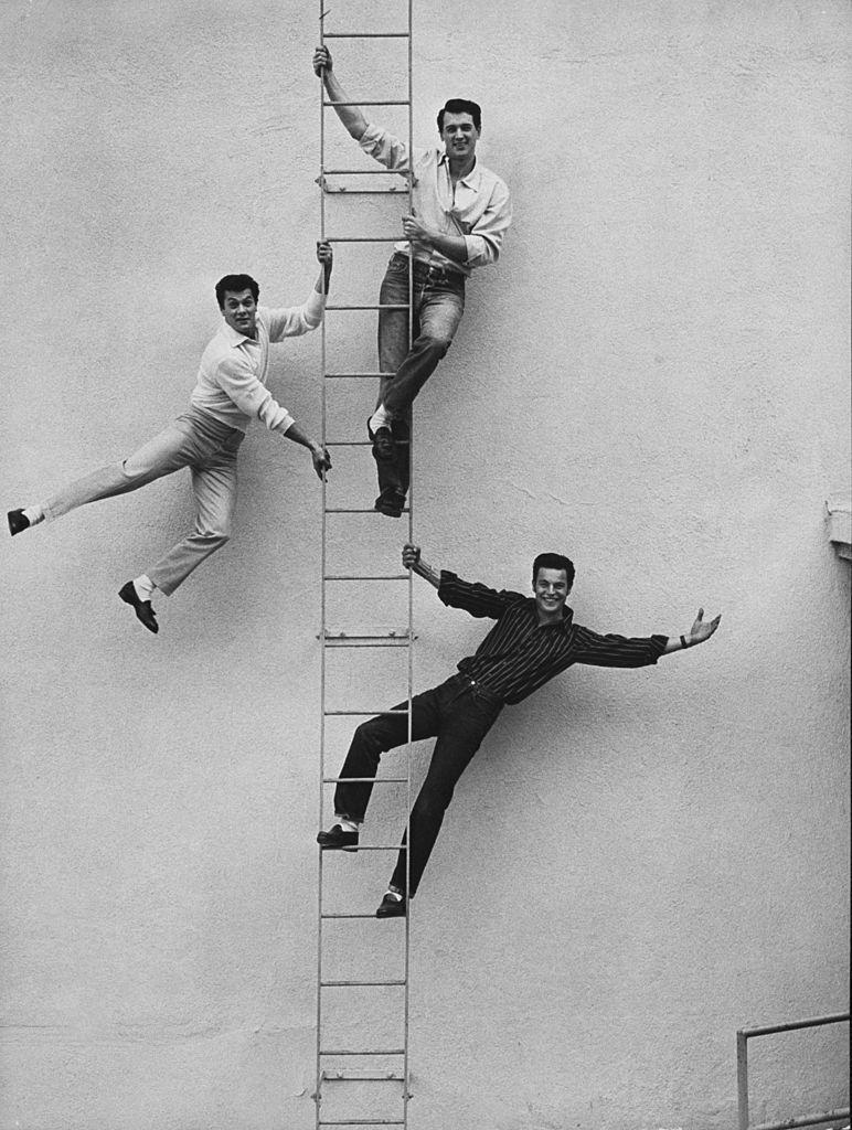 <p>From top to bottom, Hudson, Tony Curtis, and Robert Wagner, all actors, posed on a ladder together. </p>