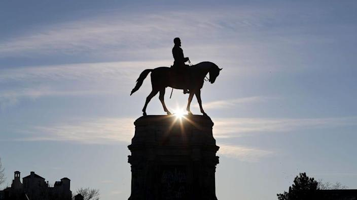 The sun rises behind the Robert E. Lee statue, where streets are closed ahead of expected protests in Richmond, Virginia on January 17, 2021. - Security officials have warned that armed pro-Trump extremists, possibly carrying explosives, pose a threat to Washington as well as state capitals over the coming week.