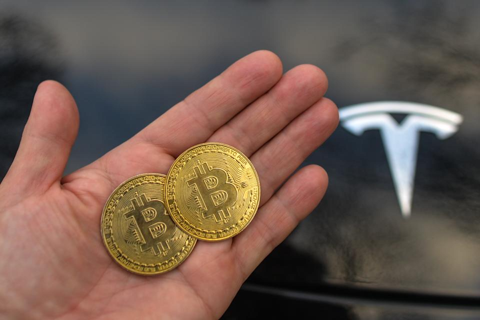 Illustrative image of two commemorative bitcoins seen in front of the Tesla car logo. On Saturday, February 27, 2021, in Dublin, Ireland. (Photo by Artur Widak/NurPhoto via Getty Images)