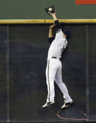 Milwaukee Brewers left fielder Ryan Braun leaps at the wall to catch a ball hit by Los Angeles Dodgers' Adrian Gonzalez during the sixth inning of a baseball game Wednesday, May 22, 2013, in Milwaukee. (AP Photo/Morry Gash)