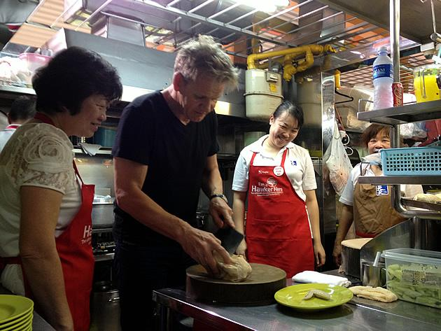 Tian Tian Chicken Rice founder chef Foo Kui Lian looks on as celebrity chef Gordon Ramsay chops a piece of chicken. (Yahoo! photo)