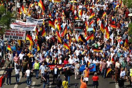 FILE PHOTO: Supporters of the Anti-immigration party Alternative for Germany (AfD) hold German flags during a protest in Berlin, Germany, May 27, 2018. REUTERS/Hannibal Hanschke/File Photo