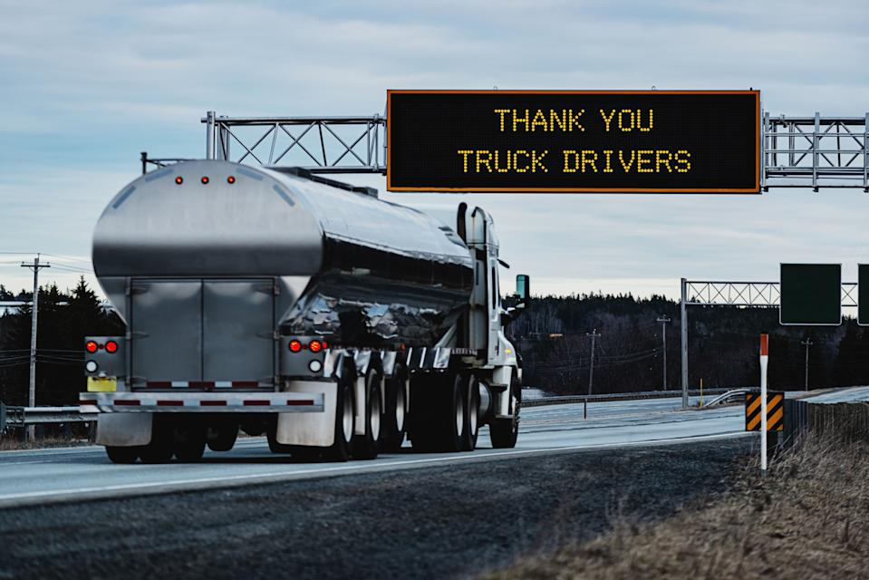 Thank You Truck Drivers on an overhead highway sign during the Coronavirus pandemic, out of focus semi truck in foreground.