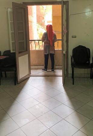 Female refugee, who complained of violent sexual assault, stands in the balcony in cairo