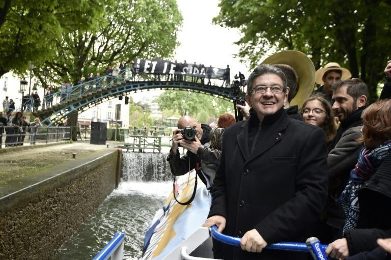 "French presidential election candidate for the far-left coalition La France insoumise Jean-Luc Melenchon (L), stands aboard an ""unbowed"" barge on the Canal Saint-Martin on April 17, 2017 in Paris"