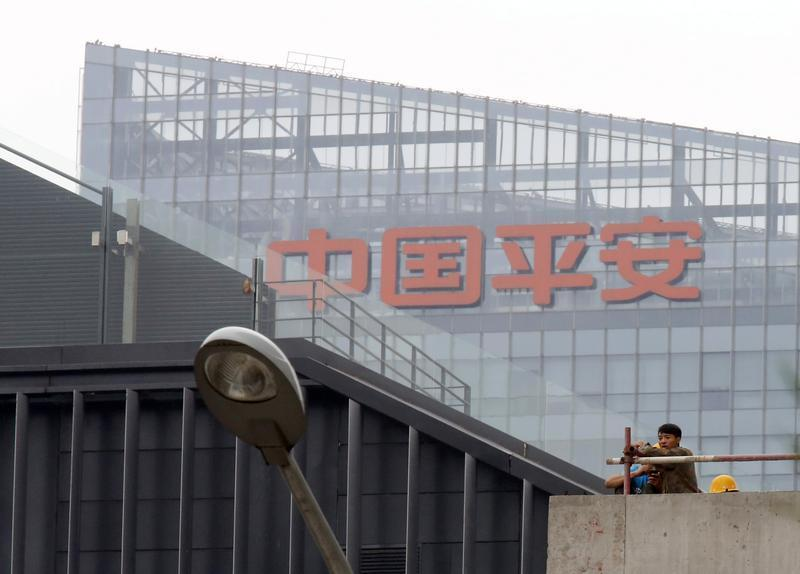 Construction workers sit on a rooftop in front of a Ping An office building in Beijing