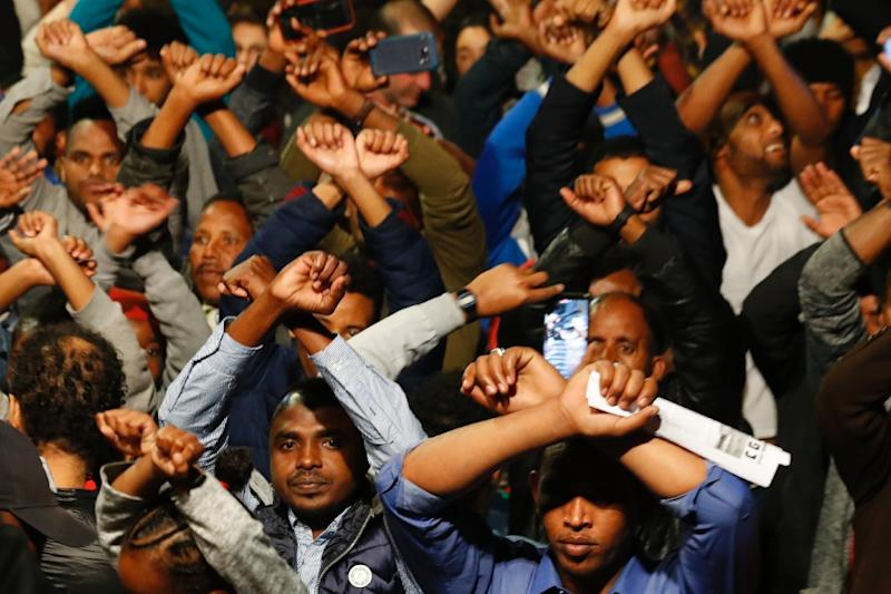African migrants demonstrate with their arms crossed in the Israeli coastal city of Tel Aviv on February 24, 2018, against the Israeli government's policy to forcibly deport African refugees and asylum seekers