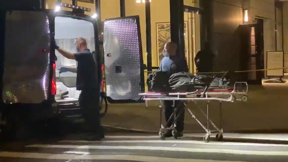 Fahim Saleh's covered body is seen in a body bag being removed from his apartment.