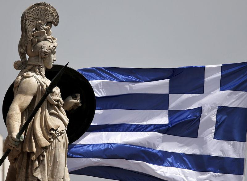 A Greek national flag flutters next to a statue of ancient Greek goddess Athena, in Athens