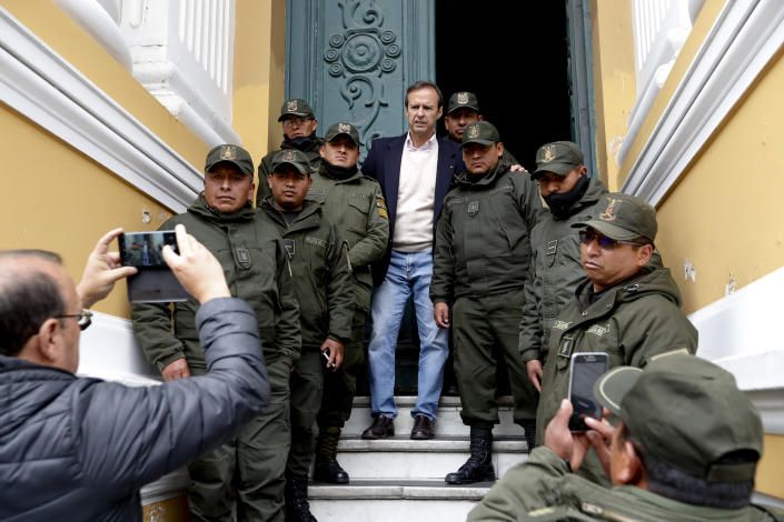 Former Bolivian President Jose Fernando Quiroga poses with police guarding Congress in La Paz, Bolivia, Monday, Nov. 11, 2019. Former President Evo Morales' Nov. 10 resignation, under mounting pressure from the military and the public after his re-election victory triggered weeks of fraud allegations and deadly demonstrations, leaves a power vacuum and a country torn by protests against and for his government. (AP Photo/Natacha Pisarenko)