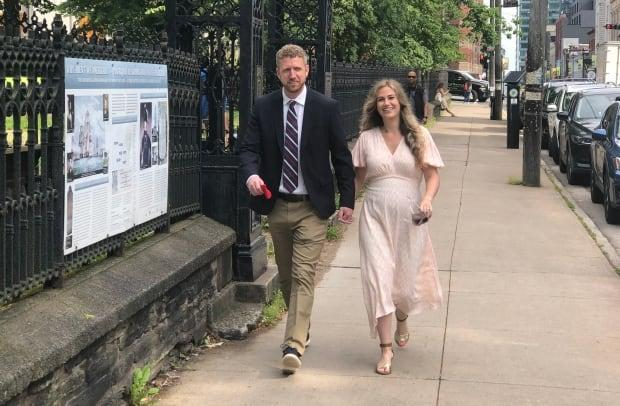 Nova Scotia Liberal Party leader Iain Rankin, left, and his wife, Mary Chisholm, walk to Government House on Saturday morning. (Jean Laroche/CBC - image credit)