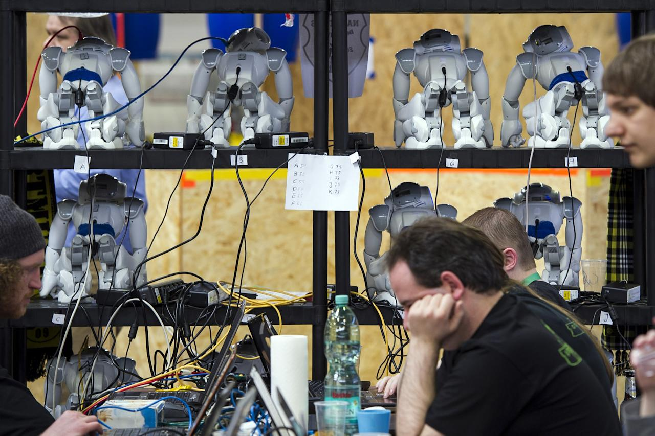 MAGDEBURG, GERMANY - APRIL 26:  Robots stand at a shelf near the play field at the 2013 RoboCup German Open tournament on April 26, 2013 in Magdeburg, Germany. The robots, which are a model called Nao, manufactured by Aldebaran Robotics, perform autonomously and communicate with one another via WLAN. The three-day tournament is hosting 43 international teams and 158 German junior teams that compete in a variety of disciplines, including soccer, rescue and dance.  (Photo by Jens Schlueter/Getty Images)