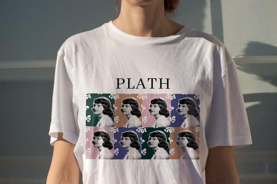 """<h2>Sylvia Plath Shirt</h2><br>Sylvia Plath is a household name in all of literature and her emotional poems resonate with the masses to this day. This shirt would be a good gift for people who don't even touch books, to be honest. <br><br><em>Shop</em> <a href=""""https://fave.co/31lKeWP"""" rel=""""nofollow noopener"""" target=""""_blank"""" data-ylk=""""slk:Artily Store"""" class=""""link rapid-noclick-resp""""><strong><em>Artily Store</em></strong></a><br><br><strong>ArtilyStore</strong> Sylvia Plath Shirt, $, available at <a href=""""https://go.skimresources.com/?id=30283X879131&url=https%3A%2F%2Ffave.co%2F2IHjBVG"""" rel=""""nofollow noopener"""" target=""""_blank"""" data-ylk=""""slk:Etsy"""" class=""""link rapid-noclick-resp"""">Etsy</a>"""