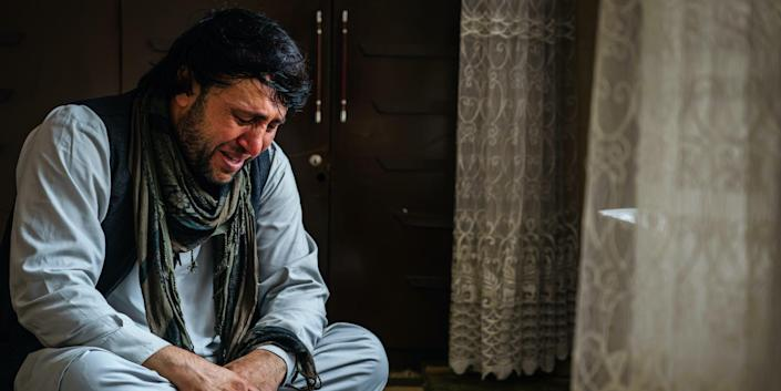 An Afghan man who lost family due to US drone strikes weeps.
