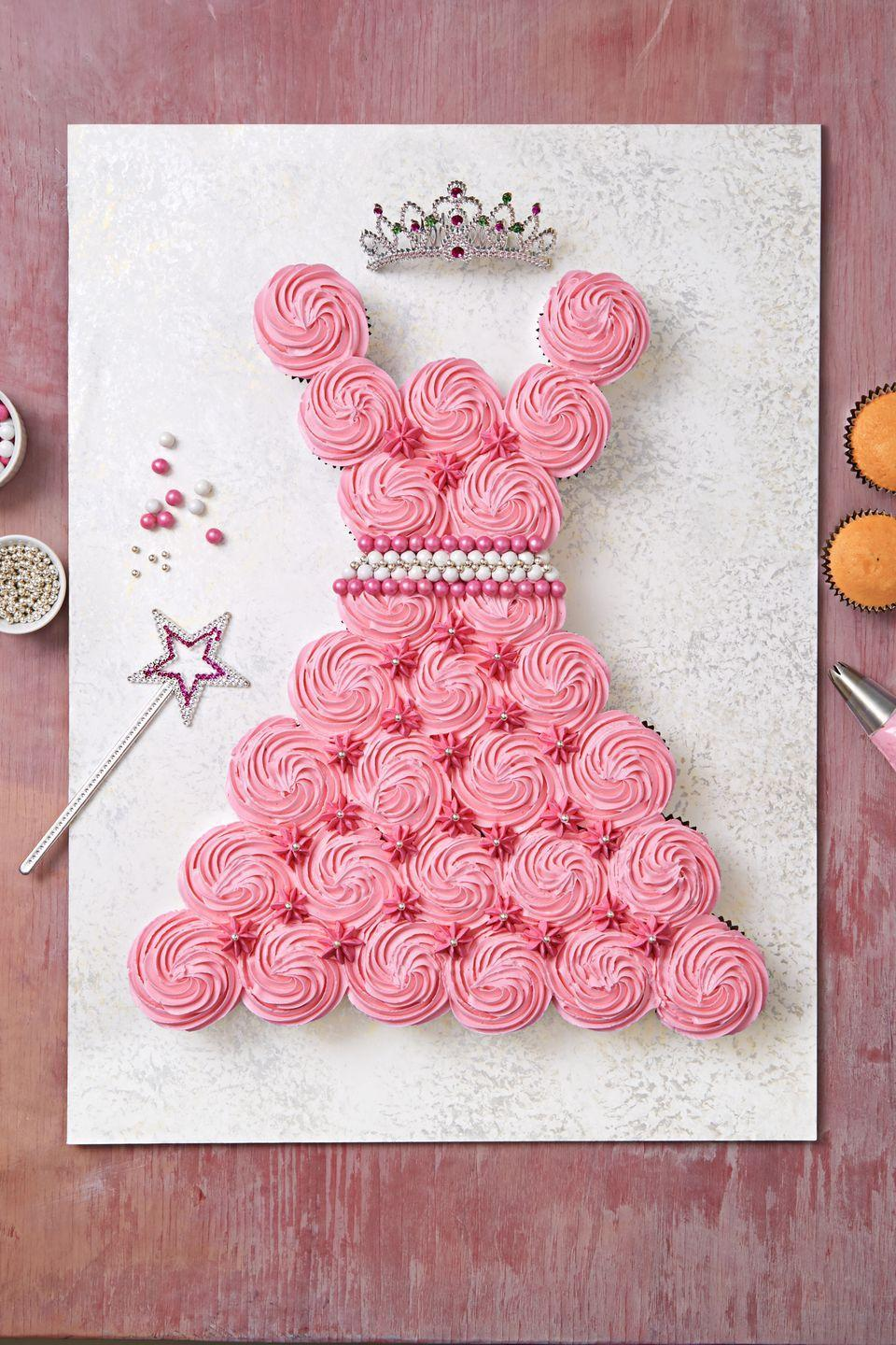 """<p>Decorate store-bought cupcakes with vanilla buttercream, arrange them in a dress pattern on cardboard, and add candy flowers to fill in the gaps.</p><p><a href=""""https://www.womansday.com/food-recipes/food-drinks/recipes/a12442/vanilla-buttercream-recipe-wdy1214/"""" rel=""""nofollow noopener"""" target=""""_blank"""" data-ylk=""""slk:Get the Vanilla Buttercream recipe."""" class=""""link rapid-noclick-resp""""><strong><em>Get the Vanilla Buttercream recipe.</em></strong></a></p>"""