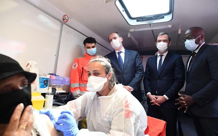 French Health Minister Olivier Veran (2ndR) watches as a woman receives a Pfizer vaccine in Paris - Alain JOCARD / AFP