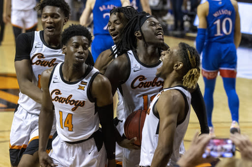 Oklahoma State's Matthew-Alexander Moncrieffe, from left to right, Bryce Williams, Kalib Boone, Isaac Likekele and Rondel Walker celebrate after the NCAA college basketball game against Kansas in Stillwater, Okla., Tuesday, Jan. 12, 2021. Oklahoma State won 75-70. (AP Photo/Mitch Alcala)