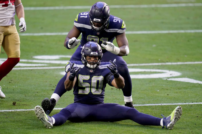 Seattle Seahawks outside linebacker K.J. Wright (50) and defensive end L.J. Collier (91) celebrate a defensive stop against the San Francisco 49ers during the first half of an NFL football game, Sunday, Jan. 3, 2021, in Glendale, Ariz. (AP Photo/Ross D. Franklin)