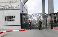 Hamas security officers stand guard the gate of the border to the Egyptian side of Rafah crossing, in Rafah, Gaza Strip, Tuesday, Aug. 11, 2020. Egypt reopened Rafah Crossing for three days starting Tuesday for humanitarian cases in and out of the Gaza Strip, including medical patients and people who had Egyptian and international citizenship. The border was closed since March. (AP Photo/Adel Hana)
