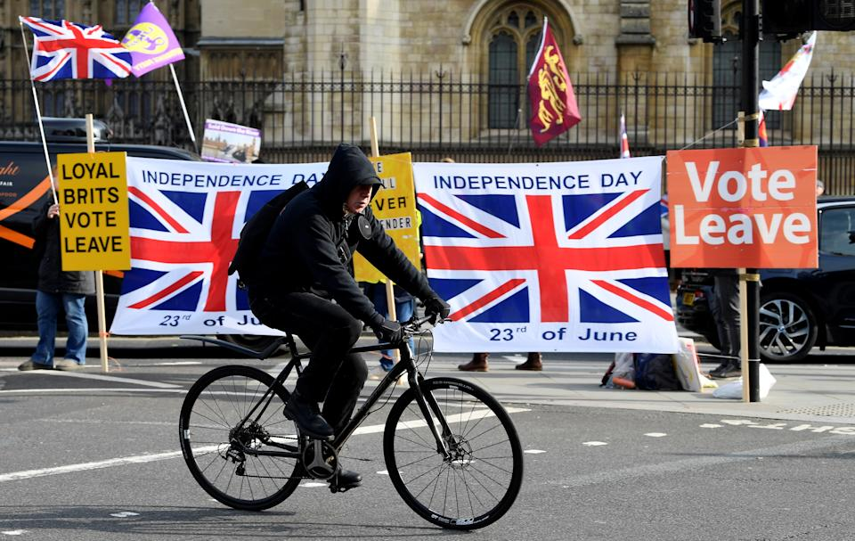 A cyclist passes pro-Brexit supporters outside the Houses of Parliament in London, Britain October 31, 2019. REUTERS/Toby Melville