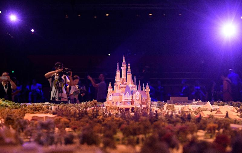 Members of the media take photos of a model of the Shanghai Disney Resort during a press event in Shanghai on July 15, 2015 (AFP Photo/Johannes Eisele)