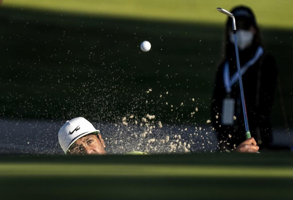 Tony Finau hits out of a bunker during a second playoff hole against Max Homa.