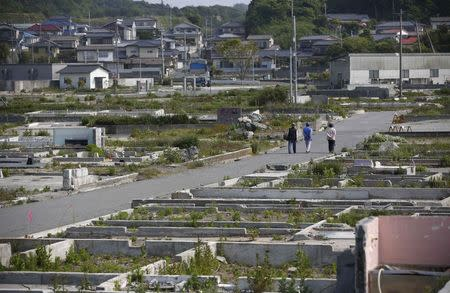 Local residents walk along a street which was devastated by the March 11, 2011 tsunami and earthquake in Iwaki, south of the tsunami-crippled Fukushima Daiichi nuclear power plant, Fukushima prefecture in this May 27, 2013 file photo. REUTERS/Issei Kato