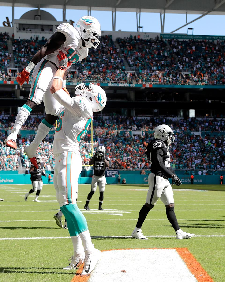 <p>Miami Dolphins tight end Mike Gesicki (86) hoists up wide receiver Jakeem Grant (19) after Grant scored a touch down during the second half of an NFL football game against the Oakland Raiders, Sunday, Sept. 23, 2018 in Miami Gardens, Fla. (AP Photo/Lynne Sladky) </p>