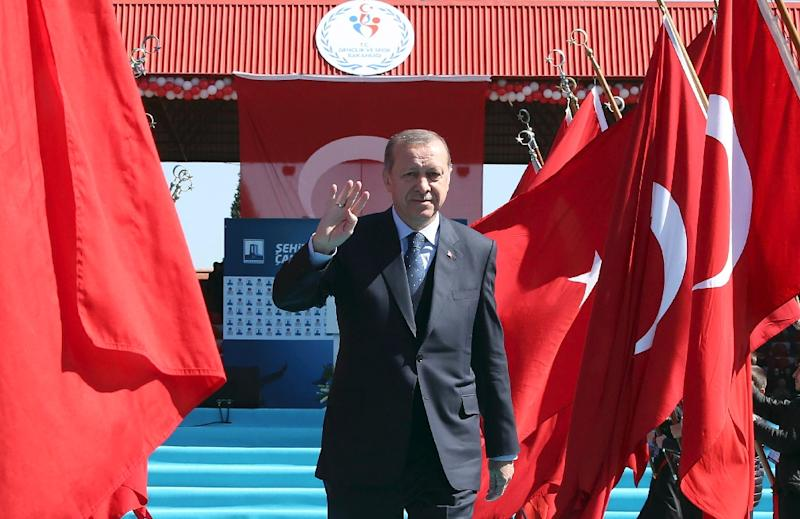 Turkish President Recep Tayyip Erdogan waves as he arrives to attend a ceremony marking the 102nd anniversary of the Canakkale Victory
