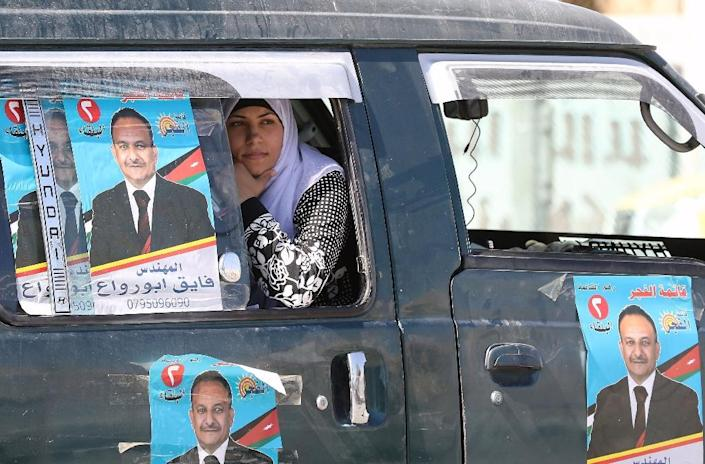 A Jordanian woman sits inside a van adorned with campaign posters outside a polling station in the capital Amman on September 20, 2016 (AFP Photo/Khalil Mazraawi)