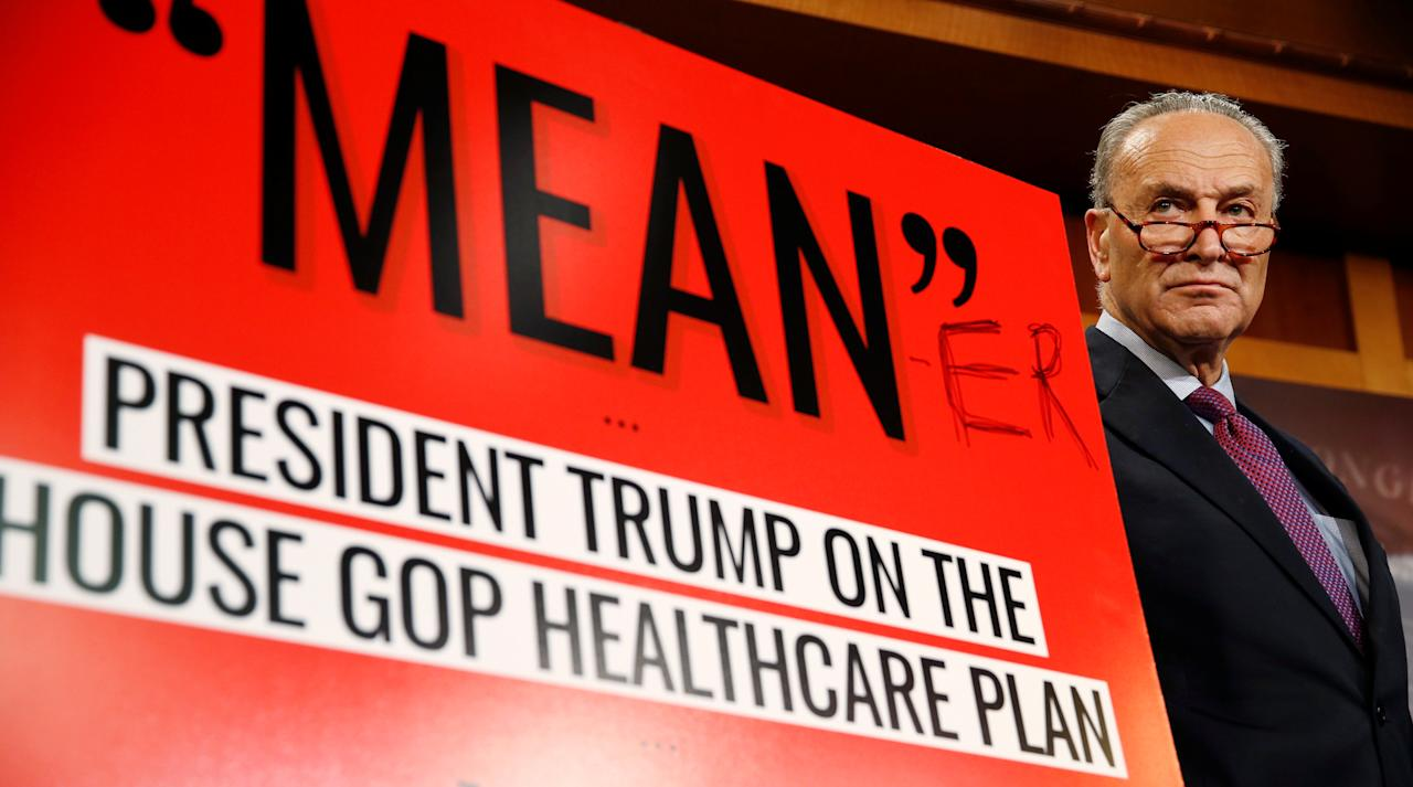 """Senate Minority leader Chuck Schumer appears at a press conference with a sign that he had personally edited to read """"Mean-er"""" after Senate Republicans unveiled their version of legislation that would replace Obamacare on Capitol Hill in Washington, U.S., June 22, 2017.   REUTERS/Joshua Roberts     TPX IMAGES OF THE DAY"""