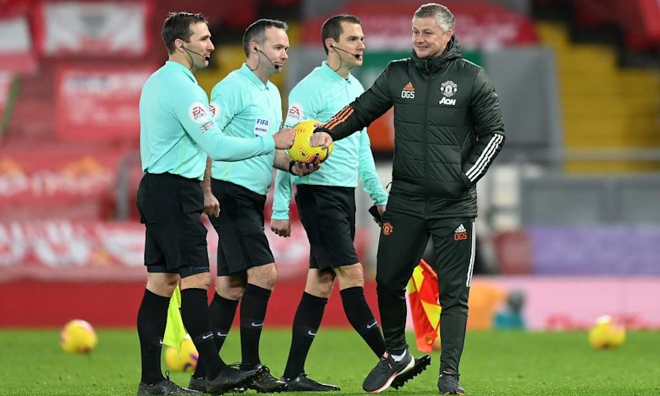 Ole Gunnar Solskjær bumps fists with the officials after the 0-0 draw at Anfield
