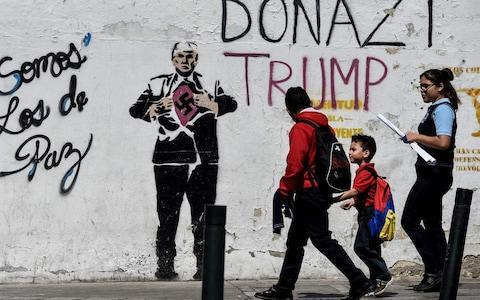 Students walk past a painting of US President Donald Trump on a wall in Caracas - Credit: JUAN BARRETO/AFP