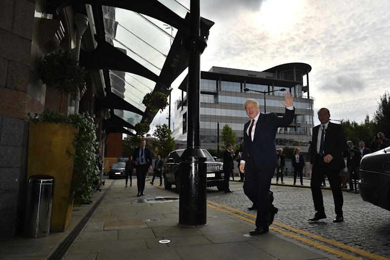 Britain's Prime Minister Boris Johnson waves as he returns to his hotel on the second day of the annual Conservative Party conference in Manchester, north-west England on September 30, 2019. - British Prime Minister Boris Johnson's office has denied allegations he made unwanted sexual advances towards two women 20 years ago. Journalist Charlotte Edwardes wrote in a column for The Sunday Times that Johnson put his hand on her thigh at a dinner party thrown by the magazine he was editing at the time. (Photo by Ben STANSALL / AFP) (Photo credit should read BEN STANSALL/AFP/Getty Images)